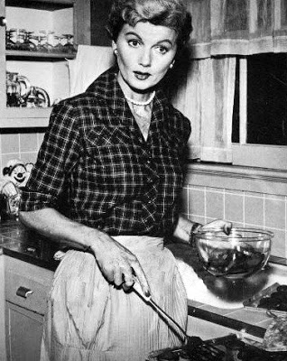 June Cleaver wearing an apron