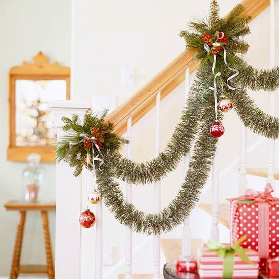 Stairway Showcase Garland  Stairway Showcase Garland  For a twist on the traditional garland-dressed banister, try this accent. Wire double swags of green tinsel garland at intervals along the banister rail, and tie ornaments dangling from silver ribbon. To add clusters of greenery and holly, tightly wrap wire around the railing for each cluster and tuck cuttings securely beneath the wire.