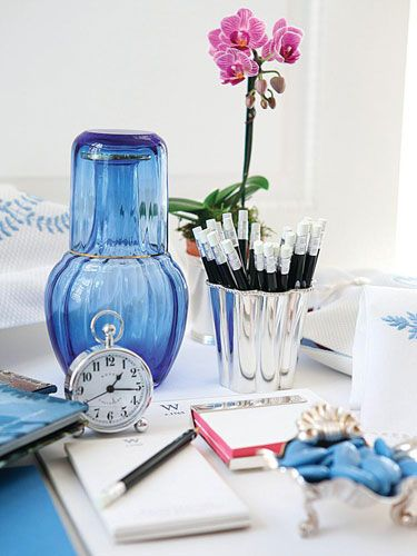 Desk space for a guest - orchid, blue water carafe, alarm clock, sharpened pencils, paper - Carolyne Roehm in Veranda: