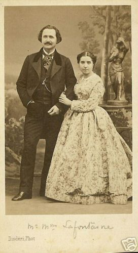 Finely dressed couple. Gent in frock coat, vest with watch chain, trousers, shirt and cravat. Lady in floral print with high body, demi open sleeves, pleated skirt.: