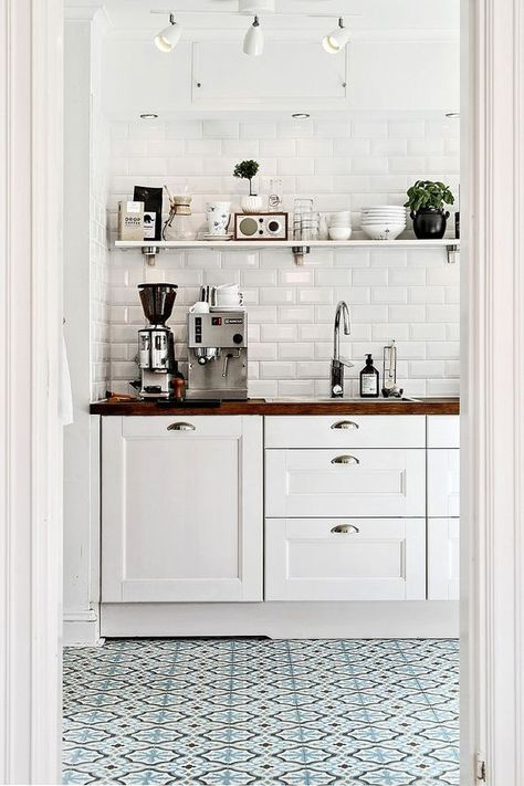 Blue printed tiles in white modern rustic kitchen, white cabinets, open shelving, butcher block counters and white subway tile: