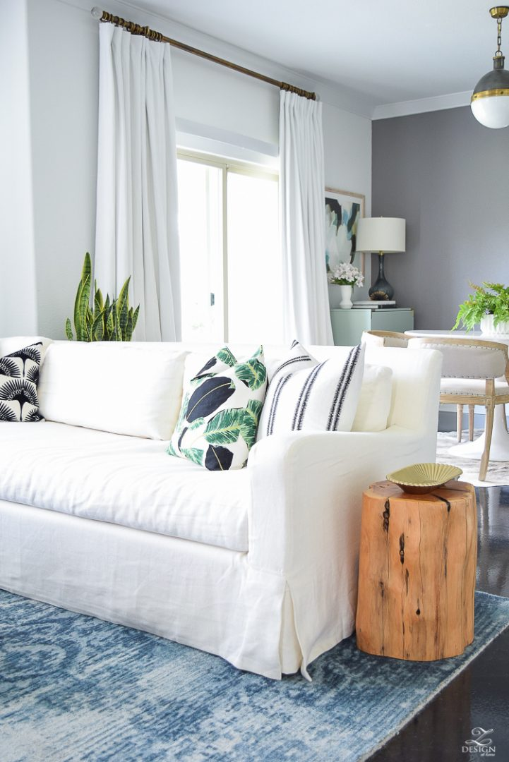 zdesign at home summer home tour blue vintage inspired rug white slip covered couch white walls white linen drapes black fur stool black and white pillows leather pillow-2