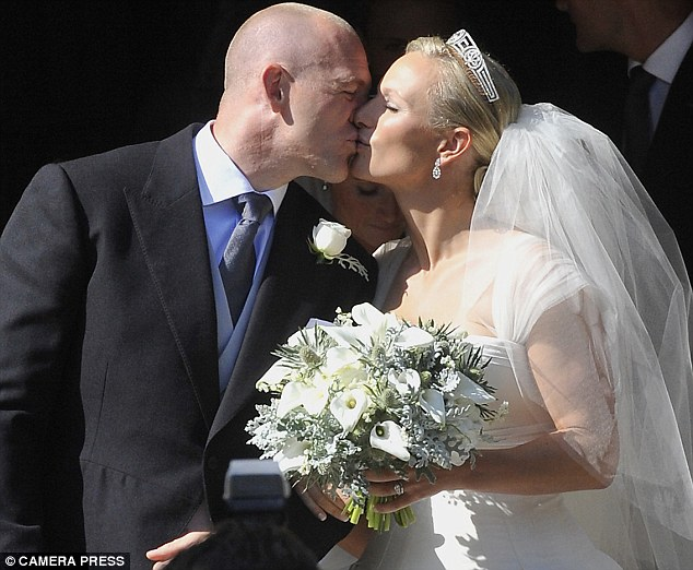 Give us a kiss! Zara Phillips and Mike Tindall share a tender embrace outside the church after getting married