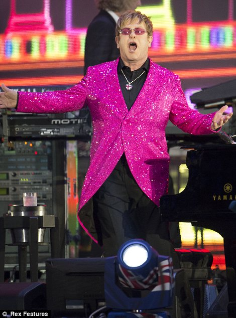 Think pink: Sir Elton John was dressed in a sparkling bright pink coat and a black suit and a pair of black trousers as he performed Your Song and dedicated it to the Queen
