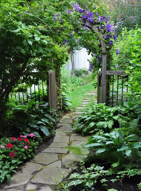 I think all gardens should have some sort of pathway. This is beautiful! Flagstone walkway and arbor.: