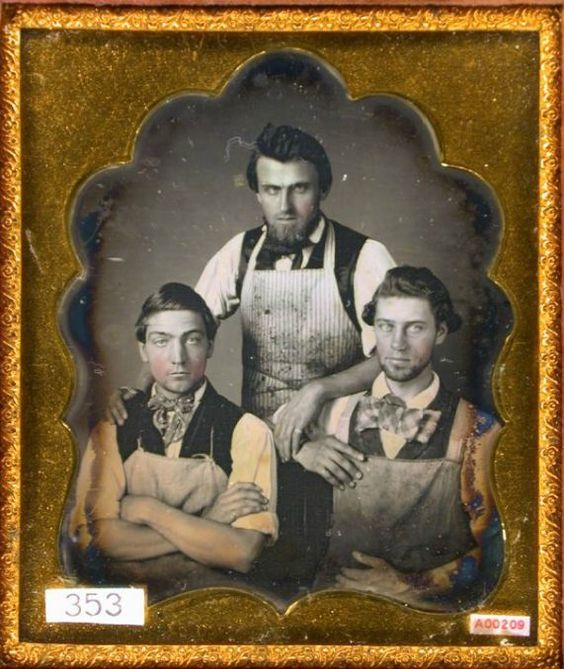 Three shop workers wearing aprons.