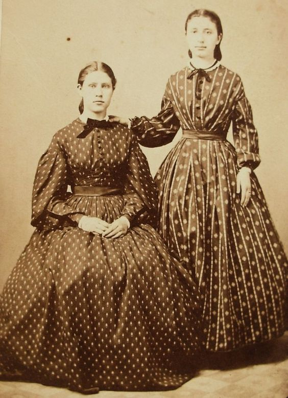 Young women wearing pretty calico dresses.
