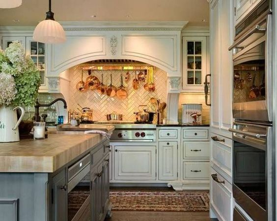 english-country-kitchen-with-white-cabinets-and-wall-mounted-pot-rack-over-range.jpg