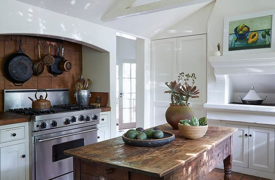 """This kitchen is not just for show. """"That stove is constantly in use,"""" says Kendall. """"And our table is always full of fresh produce from our garden."""" A silver ice bucket corrals wooden spoons beneath iron and copper pots. A painting by Kendall's sister, Cayetana hangs above a traditional tagine."""